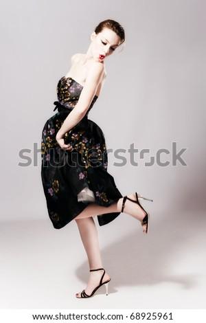 young woman in elegant high fashion dress, studio shot, full body shot - stock photo