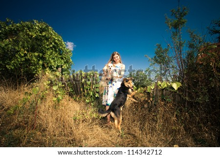 young woman in elegant silky dress with two cute dogs at countryside autumn sunny day - stock photo