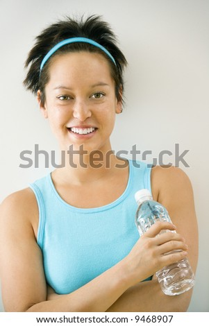 Young woman in exercise clothes holding bottle of water smiling. - stock photo