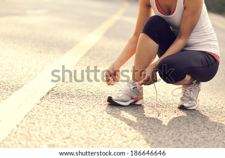 young woman in fitness wear ties shoelaces outdoors