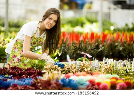 Young woman in flower garden - stock photo