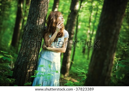 Young woman in forest. Dark saturated colors.
