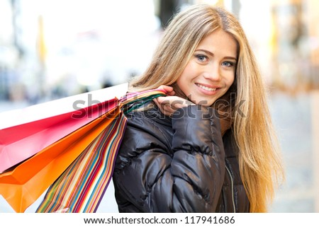 Young woman in front of a window shop and holding shopping bag - stock photo