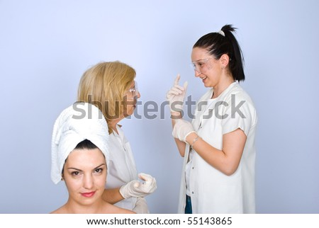 Young woman in front of camera waiting for procedure while two doctors having a conversation in background