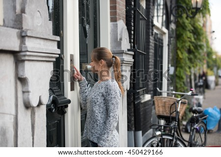 young woman in front of entrance door, ringing at the door bell - stock photo