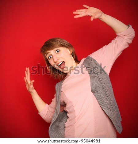 young woman in front of red background flinching - stock photo