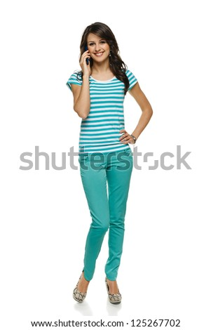 Young woman in full length talking on cellphone, over white background - stock photo