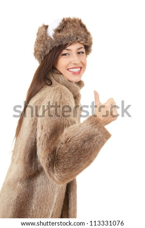 young woman in fur coat and hat with thumb up, white background - stock photo
