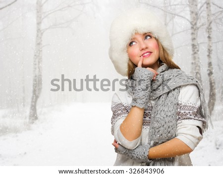 Young woman in fur hat at snowy forest - stock photo