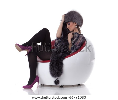 Young woman in fur  sit on armchair on a white background. - stock photo