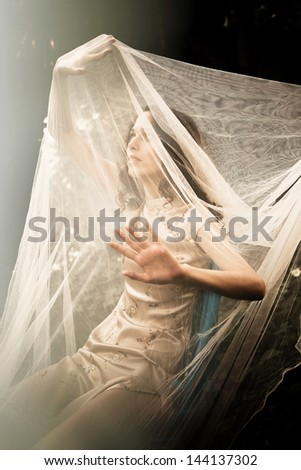 young woman in garden with veil cover her and sun light in front of her - stock photo