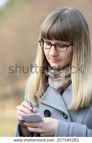 Young woman in glasses making notes using small notebook.