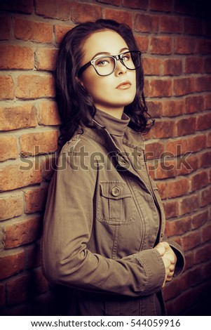 Young woman in glasses standing by the brick wall. Business casual style. Optics.