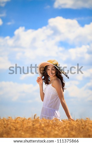 Young woman in golden wheat field enjoying in summer day