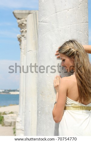 young woman in Greek style near the columns - stock photo