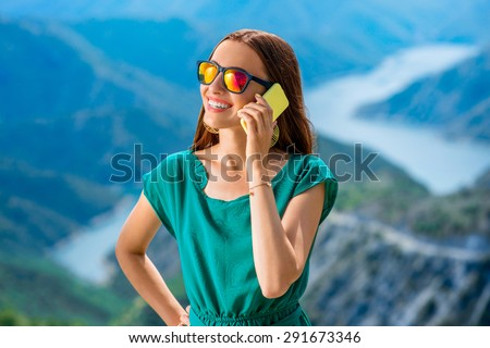 Young woman in green dress communicating with mobile phone on the top of mountain with beautiful canyon on background. Good mobile connection concept