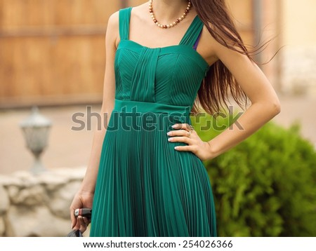 young woman in green dress standing in yard - stock photo