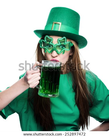 young woman in green hat and shamrock eyeglasses is drinking green beer from a mug