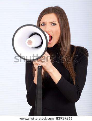 young woman in grey sweatshirt with megaphone - stock photo