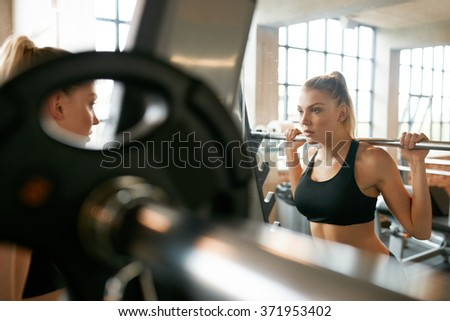 Young woman in gym doing squats with extra weight on shoulders. Fitness female working out in front of mirror at health club.