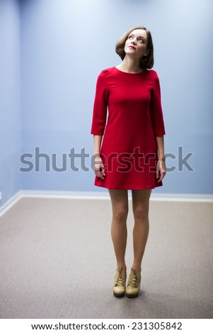 Young woman in hallway looking up on light - stock photo