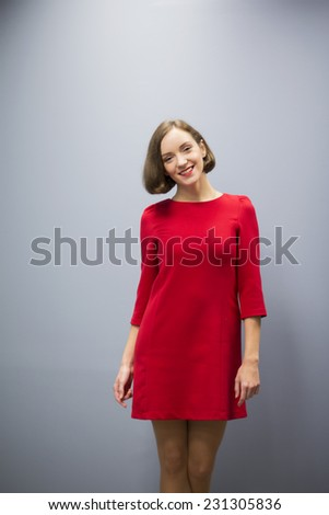 Young woman in hallway on gray wall background - stock photo