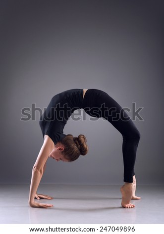 Young woman in handstand position - stock photo