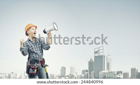 Young woman in hardhat screaming in megaphone - stock photo