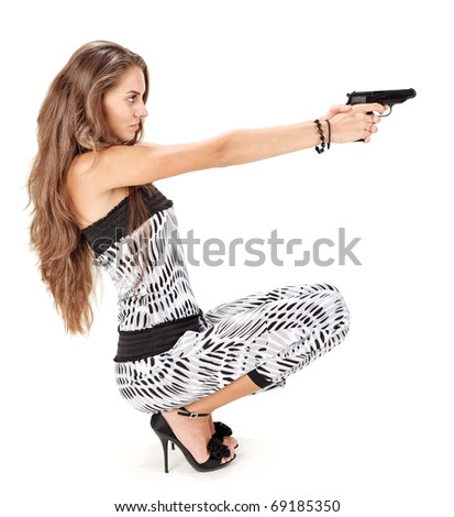 Young woman in harem pants aiming with black pistol on white