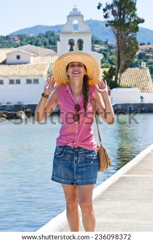 Young woman in hat enjoying her vacation time - Kanoni, Corfu town, Greec