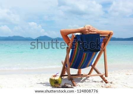 Young woman in hat sitting on tropical beach