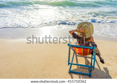 Young woman in hat sitting on tropical beach - stock photo