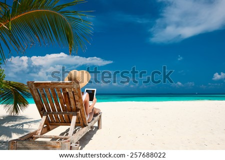 Young woman in hat with tablet pc at the beach - stock photo