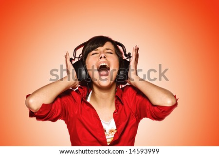 Young woman in headphones singing her favorite song - stock photo