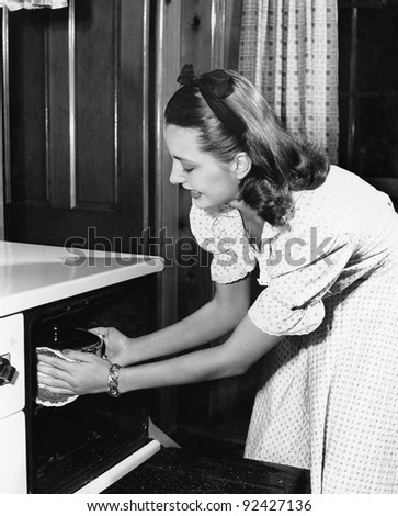 Young woman in her kitchen pulling a pot out of the oven - stock photo
