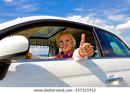 Young woman in her new car, with thumb up - stock photo