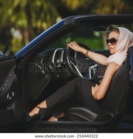 Young woman in her new convertable car smiling. Beautiful women driving a cabrio wearing accesoriess and sunglasses. Portrait of beautiful young woman with makeup in fashion clothes on hature - stock photo