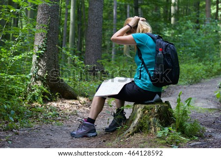 Young woman in hiking boots sitting on a tree stump with a tourist map and adjusts her hair, forest hiking trail