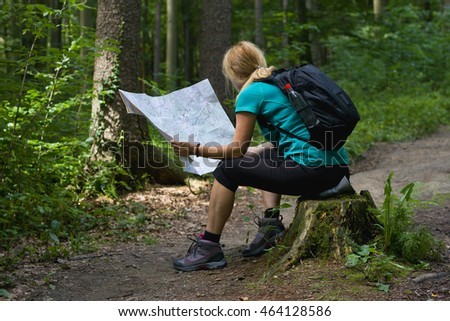 Young woman in hiking boots sitting on a tree stump with a tourist map, forest hiking trail