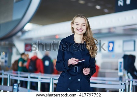 Young woman in international airport, giving her passport to an officer - stock photo