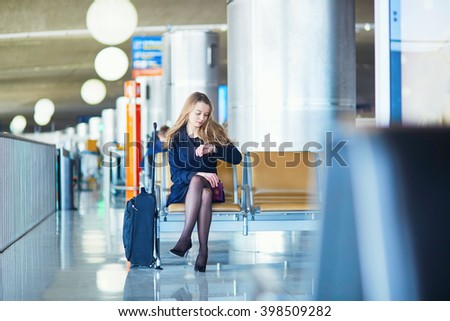 Young woman in international airport, waiting for her flight, checking her watch and looking upset or worried. Missed, canceled or delayed flight concept