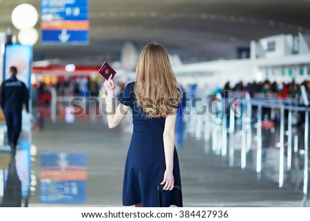 Young woman in international airport, walking with her luggage and holding French passport, back view. Flight attendant going to meet her crew - stock photo