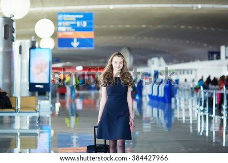 Young woman in international airport, walking with her luggage. Flight attendant going to meet her crew - stock photo