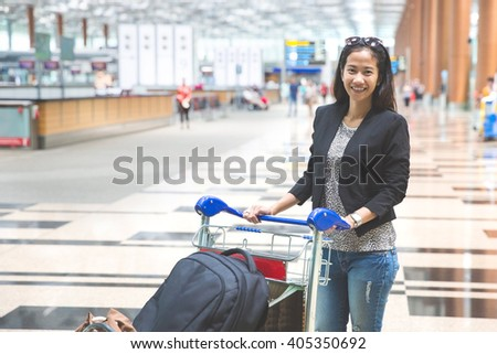 Young woman in international airport, with luggage trolley - stock photo