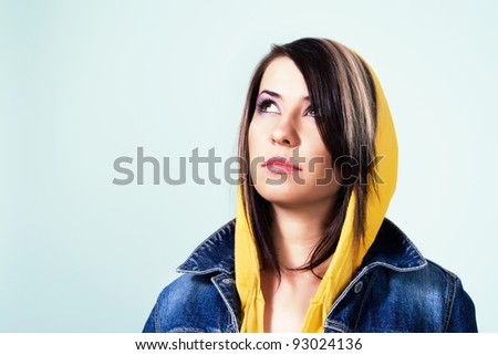 Young woman in jean jacket and yellow hood looking up - stock photo