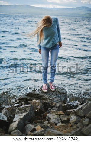 Young woman in jeans and pullover spending weekend by the seaside - stock photo