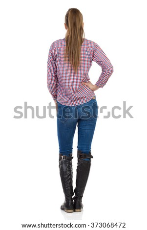 Young woman in jeans, black boots and lumberjack shirt standing with hand on hip. Rear view. Full length studio shot isolated on white. - stock photo