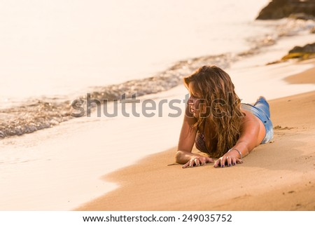 young woman in jeans on the beach - stock photo
