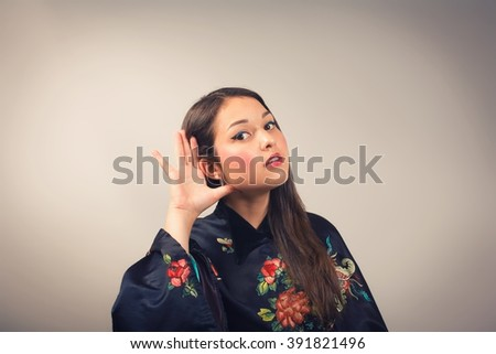 Young woman in kimono overhears. On a gray background. - stock photo