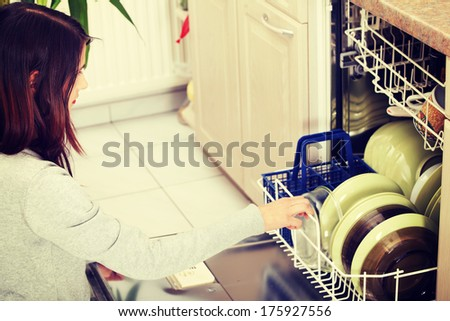 Young woman in kitchen doing housework. Puling out dishes from dishwasher - stock photo